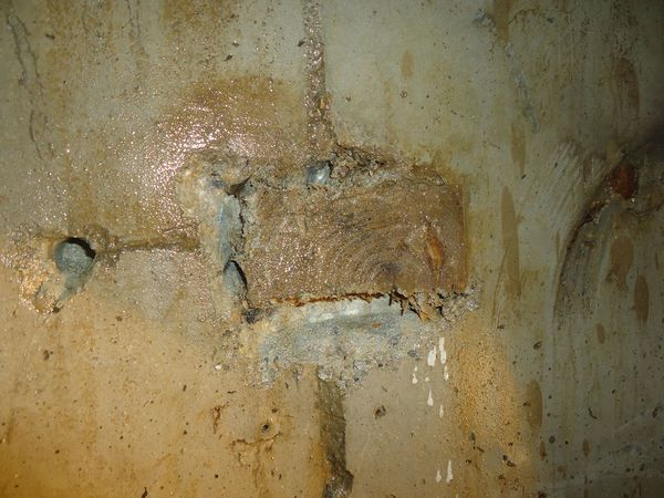 Деревянная доска в бетоне стены